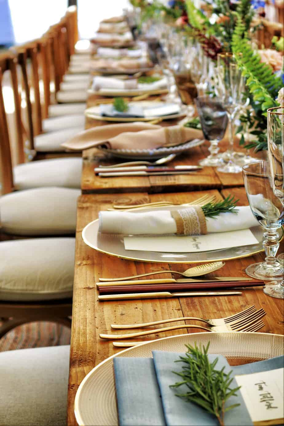Close-up photo of dinnerware laid out on long dining table.